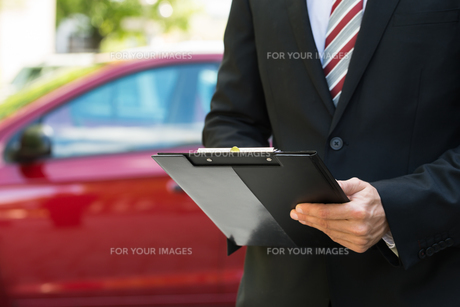 Close-up Of Male Holding Clipboard Near Car FYI00654148