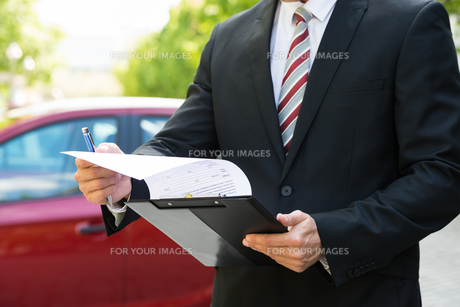 Close-up Of Male Holding Clipboard Near Car FYI00654155
