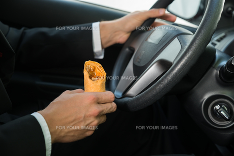 Close-up Of A Male Holding Snack While Driving FYI00654179