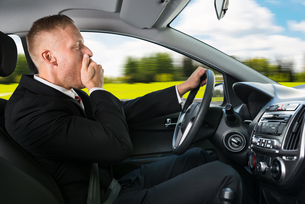 Businessman Yawning While Driving Car FYI00654186