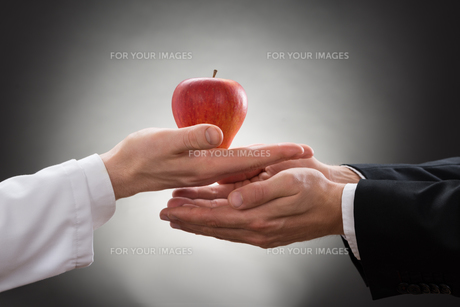 Doctor Giving Apple To A Person FYI00657174