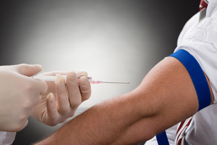 Doctor Injecting Syringe On Patient's Arm FYI00657189