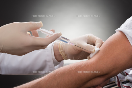 Doctor Injecting Syringe On Patient's Arm FYI00657191