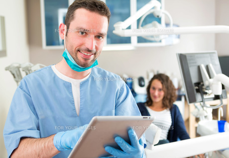 Portrait of a young attractive dentist in his office FYI00659649