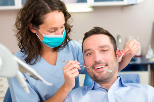 Young attractive man being cured by a dentist FYI00659663
