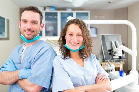 Portrait of a young attractive dentist and his assistant in his office FYI00659665