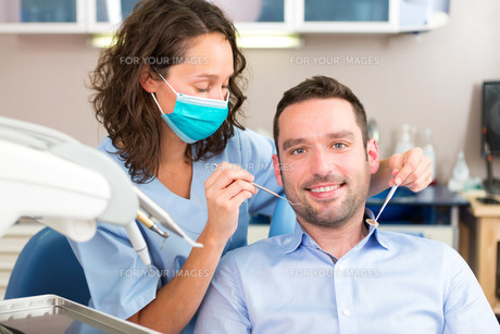 Young attractive man being cured by a dentist FYI00659667