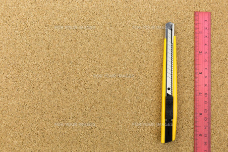 cutter and ruler on cork board FYI00661455