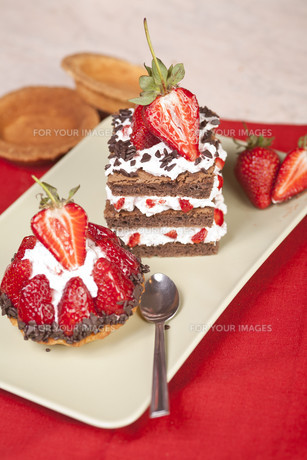Strawberry fruit tart and chocolate strawberry cake on a plate FYI00663458