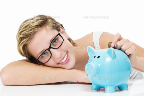 happy woman throwing coin piggy bank in her FYI00668422