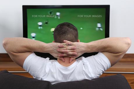 young man looks football on tv FYI00673033