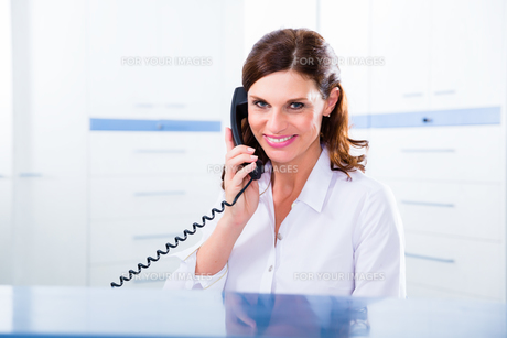receptionist in doctor's office with phone FYI00739697