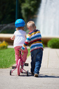 Boy and girl in park learning to ride a bike FYI00752630