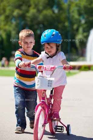 Boy and girl in park learning to ride a bike FYI00752642