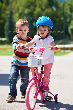 Boy and girl in park learning to ride a bike FYI00752647