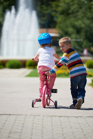 Boy and girl in park learning to ride a bike FYI00752654