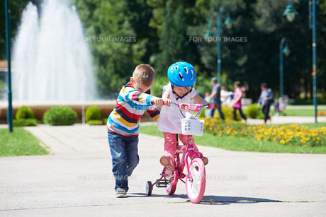 Boy and girl in park learning to ride a bike FYI00752659