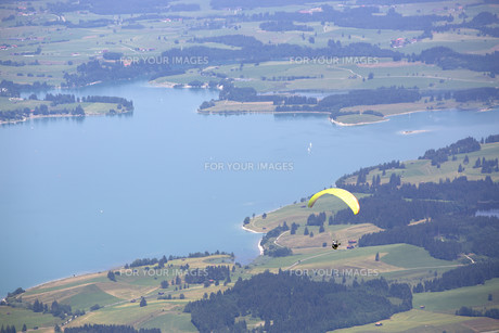 Paraglider flying over Bavarian lake FYI00753862