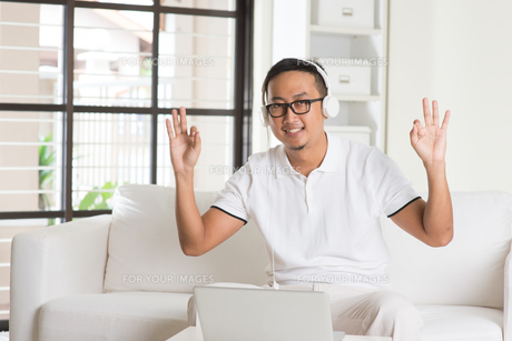 Handsome Asian man using tablet computer. Smiling Southeast Asian college student relaxing and listening to music at home. Asian model. FYI00755486