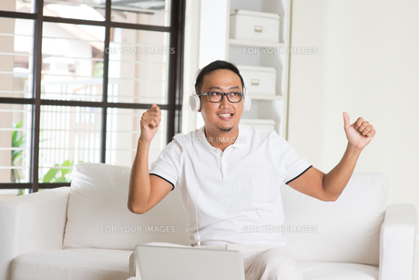 Handsome Asian man using tablet computer. Smiling Southeast Asian college student relaxing and listening to music at home. Asian model. FYI00755496