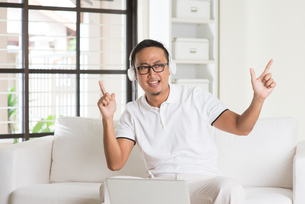 Handsome Asian man using tablet computer. Smiling Southeast Asian college student relaxing and listening to music at home. Asian model. FYI00755497