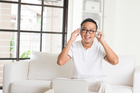 Handsome Asian man using tablet computer. Smiling Southeast Asian college student relaxing and listening to music at home. Asian model. FYI00755509
