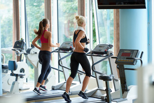 woman exercising on treadmill in gym FYI00775297