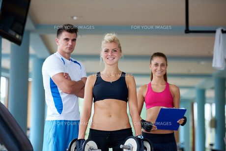 young woman in fitness gym lifting  weights FYI00775300