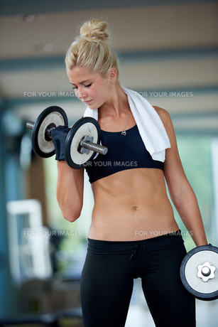 lifting some weights and working on her biceps in a gym FYI00775312