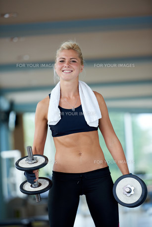 lifting some weights and working on her biceps in a gym FYI00775324