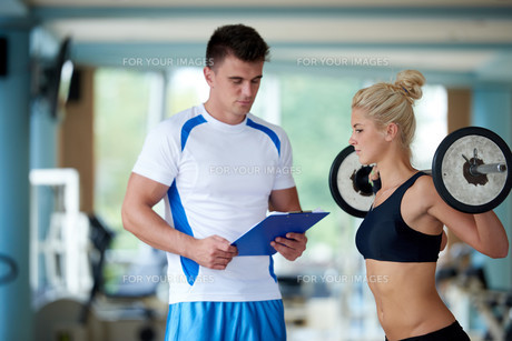 young sporty woman with trainer exercise weights lifting FYI00775329
