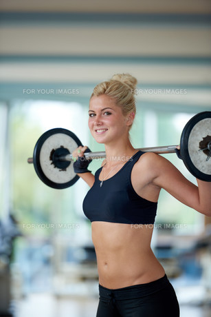 young woman in fitness gym lifting  weights FYI00775331