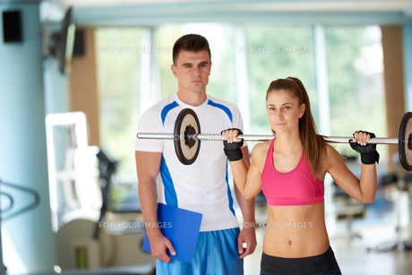 young sporty woman with trainer exercise weights lifting FYI00775336