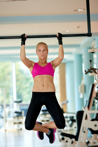 young woman in fitness gym lifting on bar FYI00776024