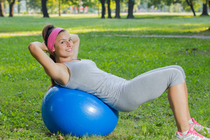 Fitness Healthy Smiling Young Woman Resting on Pilates Ball FYI00776031