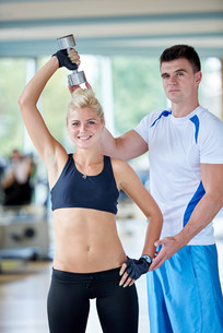 young sporty woman with trainer exercise weights lifting FYI00776050