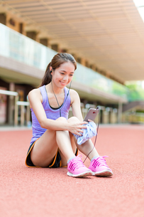 Sporty Woman listen to music and look at the cellphone FYI00785158