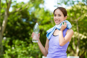 Woman with water bottle and towel after doing sport FYI00785216