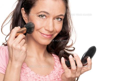 woman putting on lipstick FYI00855310
