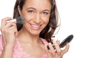 woman putting on lipstick FYI00855321