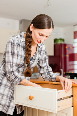 young woman builds on cabinet or from FYI00860367