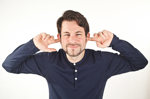 young man covering ears from loud noise,isolated on white backg FYI00873238