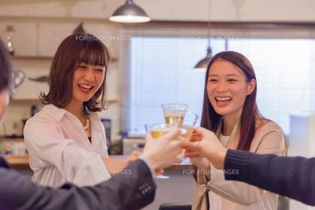 仲間と笑顔で乾杯する若い女性 FYI00894399