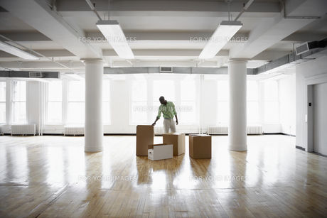 Man unpacking boxes in empty office FYI00899521