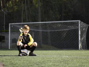Boy on soccer ball holding trophy FYI00900006