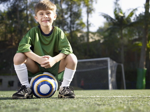 Boy sitting on soccer ball FYI00900028