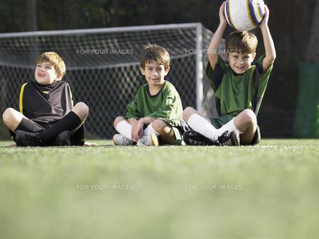 Three boys sitting in soccer field FYI00900038