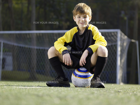Young boy sitting on soccer ball FYI00900054