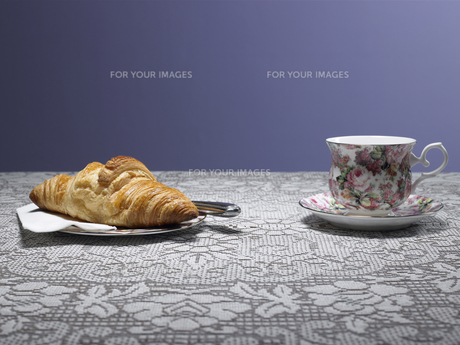 Tea cup and croissant on table FYI00900135