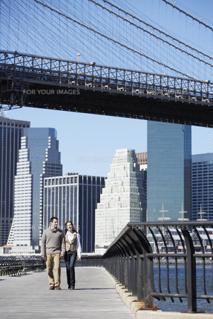 Couple walking under Brooklyn Bridge FYI00900226